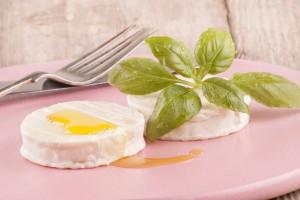 Queso de cabra con aceite de oliva y albahaca en una tabla con un tenedor