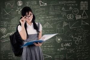 Adolescente con lentes al fondo un pizarrón con formulas y datos escolares