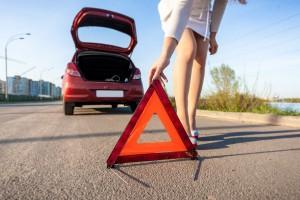 Mujer colocando señal de adventencia en carretera