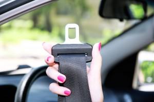 Mano de una mujer sosteniendo cinturón de seguridad en un coche