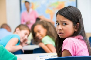 Niña volteando con mirada temerosa al fondo salón de clases