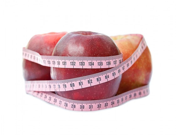 Red apple with tape on white background (health and diet concept)