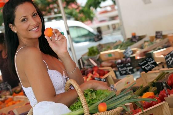 Mujer sosteniendo fruto naranja en un mercado