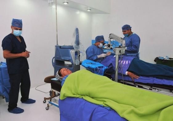 Cirukanos de pie en sla de operación con un paciente