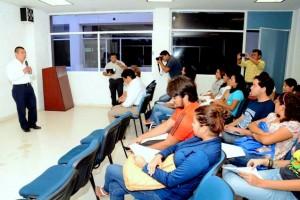 Grupo deprsonas sentadas escuchando exposición