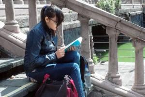 Mujer adolecente sentada en unas escaleras al fondo un puente y un cuerpo de agua