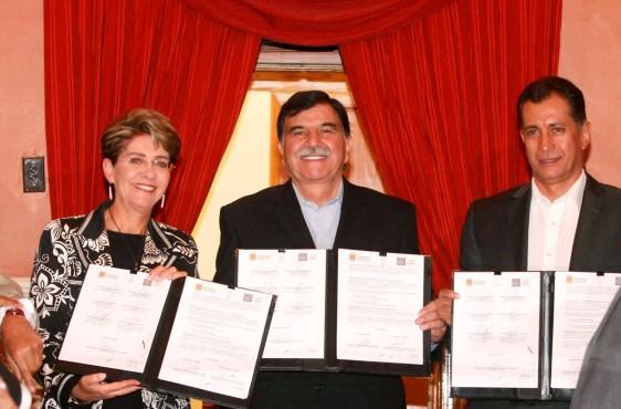 De izquierda a derecha Mercedes Juan, Mario Anguiano Moreno y Mariano González Zarur sosteniendo un documento