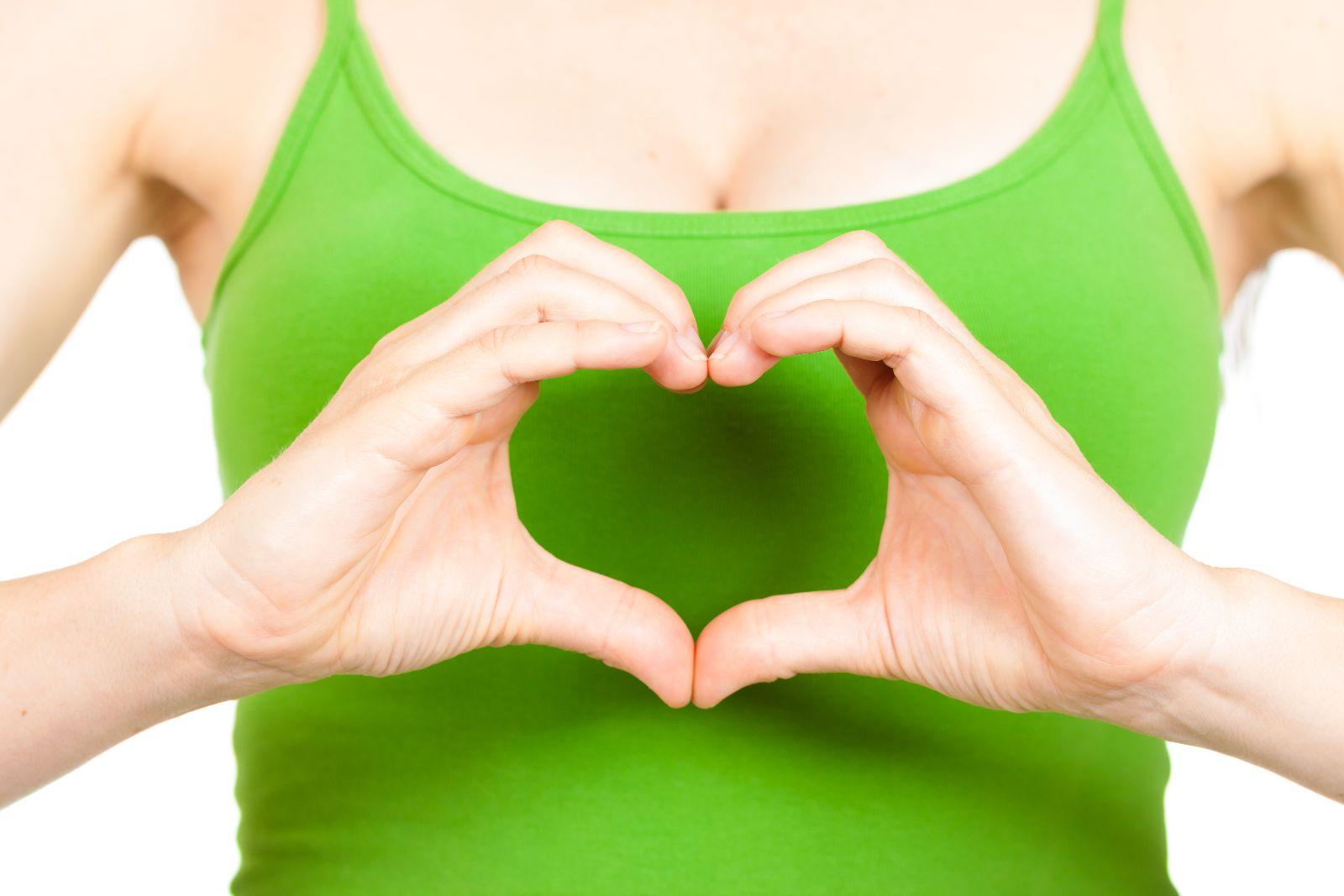 Mujer con camiseta verde hace con sus manos un símbolo de corazón