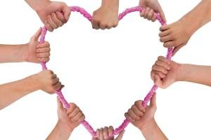 manos de mujeres forman un corazón con un mecate rosa