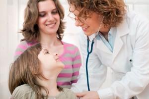 Doctora revisa co estetoscopio a una niña en el fondo una mujer observando