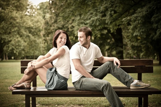 Pareja joven sentados en una banca de un parque
