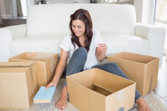 mujer desempacando cajas con sala en l fondo