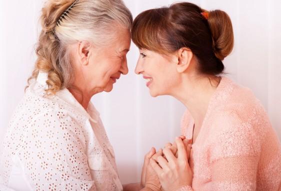 Adulta mayor con mujer joven mirándose de frente y sonriendose