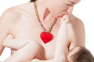 Madre con collar de corazón amamantanfo a su bebé