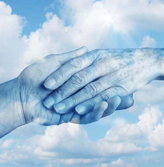 Mano de un joven con la de un anciano en un cielo azul