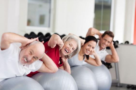 Mujer mayor sonriendo en un ginnacio con otras personas haciendo ejercicio sobre una pelota