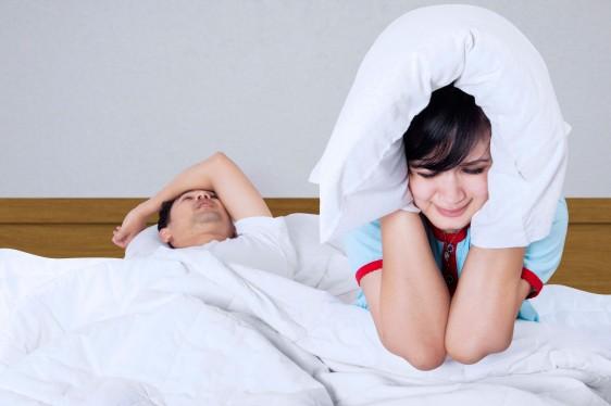 Hombre dormido y roncando al lado una mujer con almohada en los oidos