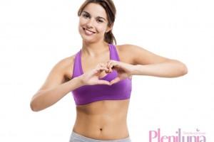 Mujer atlética en ropa deportiva haciendo con sus manos un simbolo de corazón