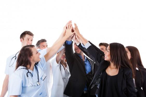 Grupo de médicos y personas en traje alzando las manos y tocando un punto común
