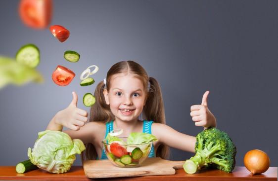 Niña con verduras mostrando sus dedos pulgares hacia arriba