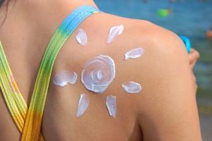 Acercamiento al hombro de una mujer en la playa con crema en forma de sol