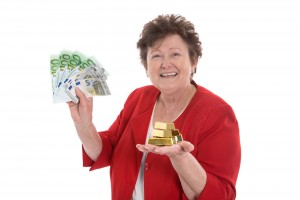 Mujer mayor feliz con billetes en la mano izquierda y barrras de oro en la mano derecha