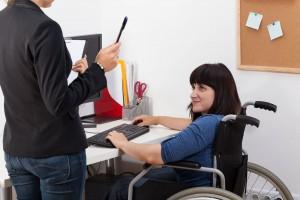 Mujer en silla de ruedas trabajando enfrente de una computadora escucha a una mujer de pie