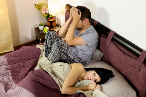 Hombre en la cama entristecido mujer dandole la espalda y viendo en otra dirección