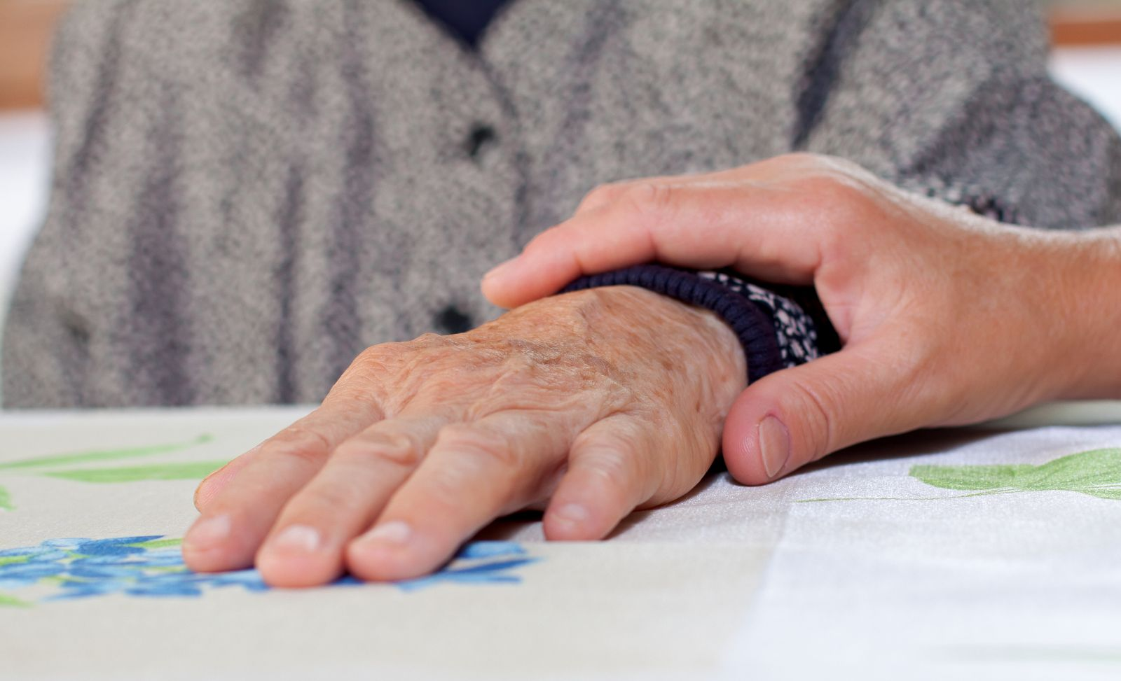Manos de un doctor sobe las manos de una adulta mayor