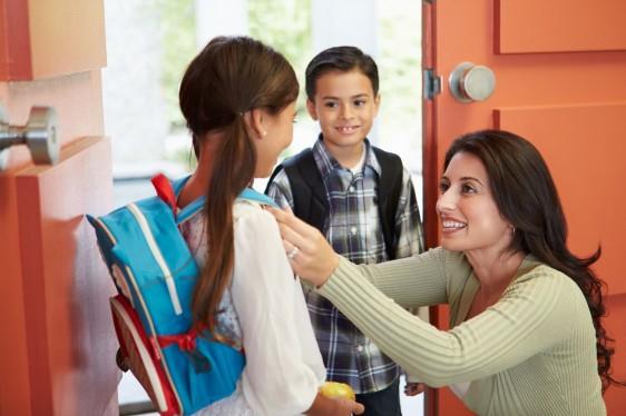 Mujer arreglando a niña con ultiles escolares y un niño al fondo los observa en una puerta