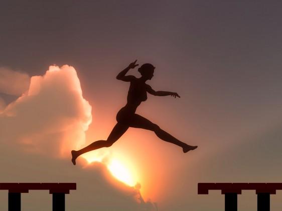 Silueta de una mujer saltando para alcanzar un escalón al fondo una puesta de sol