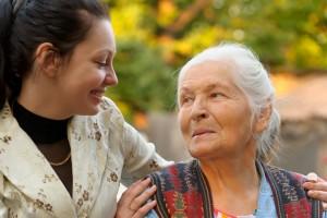 Mujer joven abrazando y sonriendo a adulta myor