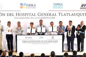 Funcionarios de pie en un podium presentando convenios firmados