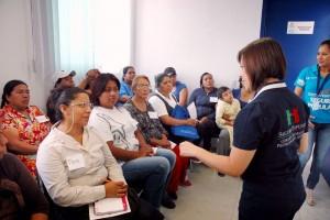 Educadora con camis del seguro popular explicando a grupo de asistentes
