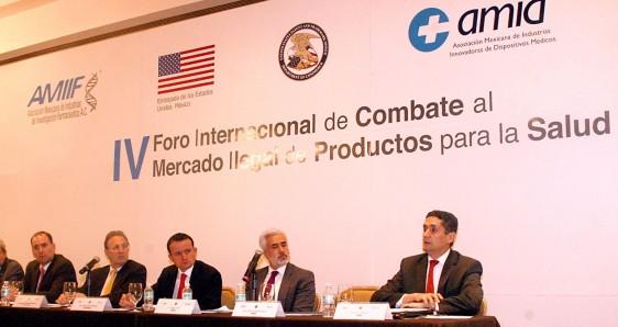 Mikel Arriola, Anthony Wayne, Miguel Ángel Margáin, entre otros sentados en una mesa al fondo un anuncio .del IV Foro Internacional de Combate al Mercado Ilegal de Productos para la Salud