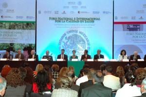 """Funcionarios en una mesa en la parte posterior letrero con texto """"Foro Nacional e Internacional por la Calidad en Salud"""""""