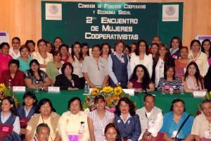 """Grupo de mujeres atrás anuncio con el texto """"2º Encuentro de Mujeres Cooperativistas"""""""