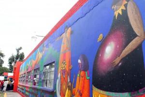 Mural mujer embarazada con galazi en el vientre