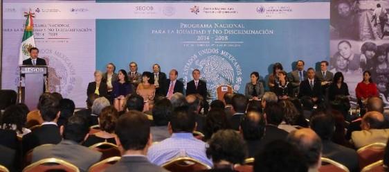 """Funcionarios en un podium con un anuncio al fondo con el texto """"Programa Nacional para la Igualdad y No Discriminación 2014 - 2018"""""""