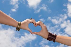 Manos unidas en forma de corazón al fondo un cielo azul