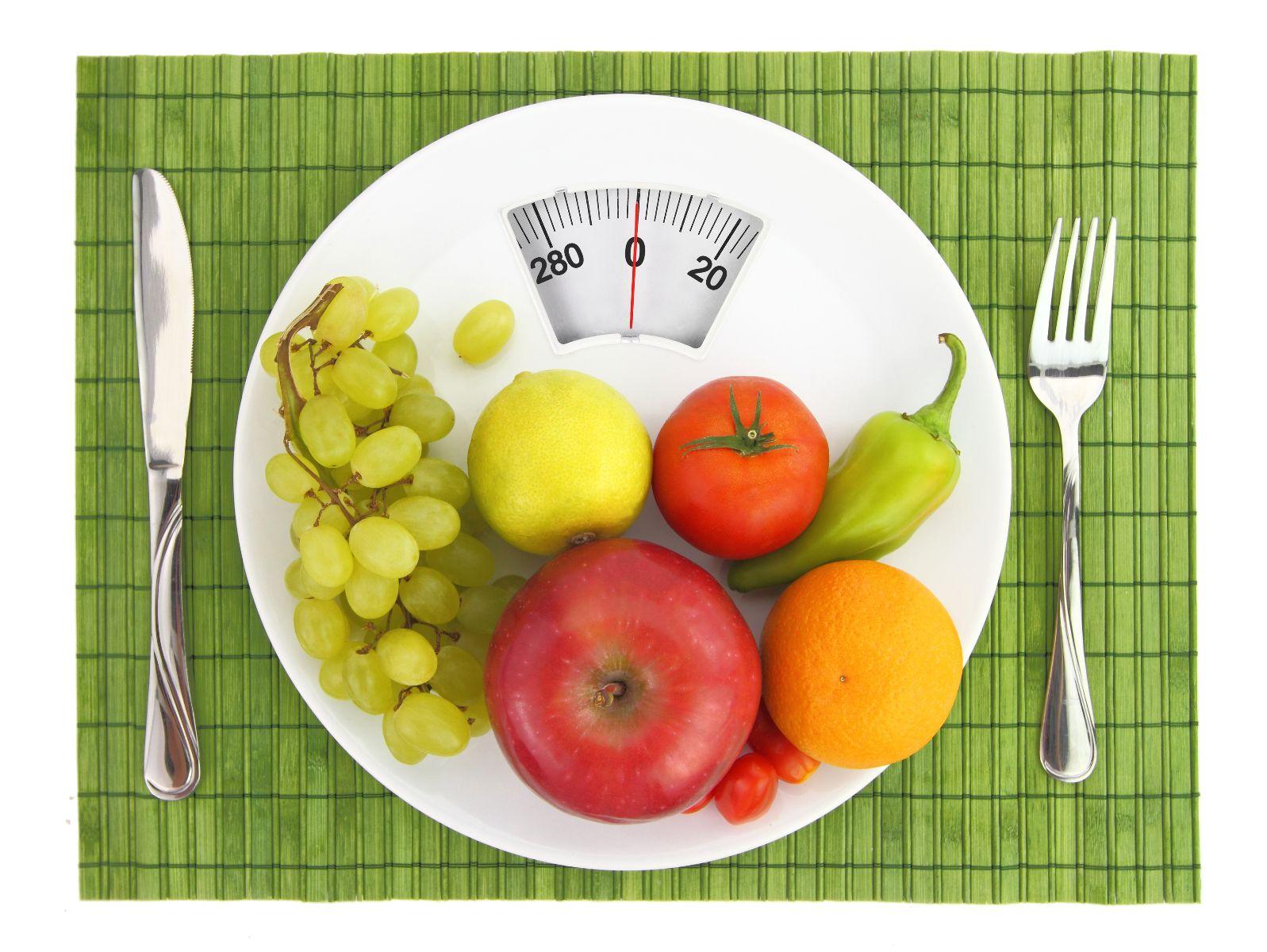Plato con frutas y cubiertos al lado arriba de una bascula