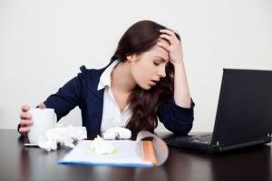 Mujer cansada sentada en odicina con una computadora