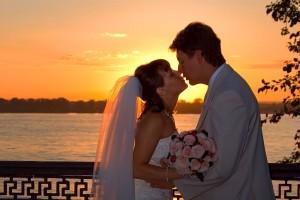 Pareja de novios besándose en la puesta de sol