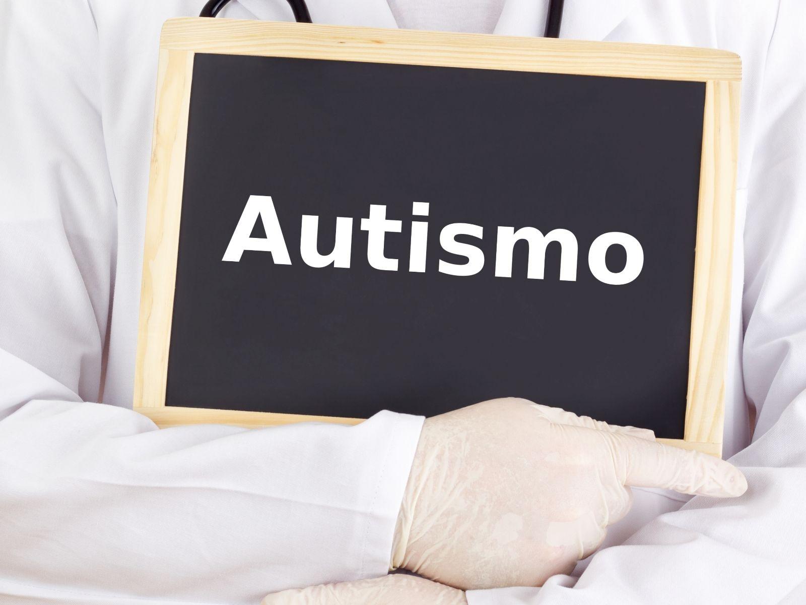 Médico sosteniendo pizarron con la palabra autismo