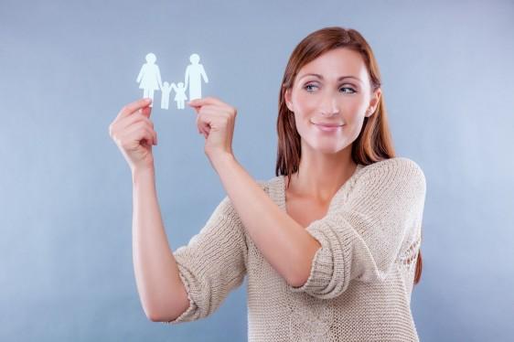 Mujer sosteniendo recorte de papel de familia en sus manos