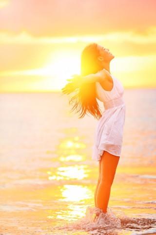Mujer abriendo los brazos en un amanecer