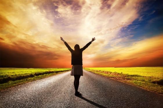 Mujer feliz abriendo los brazos en un atardecer con un largo camino enfrente