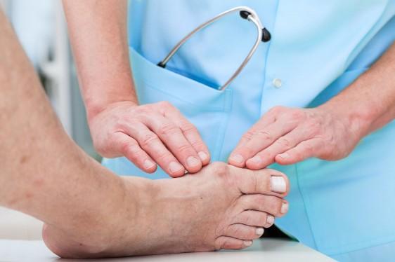 Acercamiento a las manos de un mèdico revisando el pie de una persona
