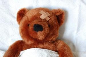 Oso de peluche en cama con curación en la cabeza