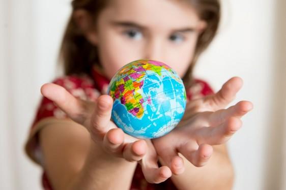 Niña sosteniendo a una pelota del mundo en sus manos